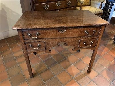 a late 18th century oak country house lowboy with carved shaped frieze on sqaure chamfered supports