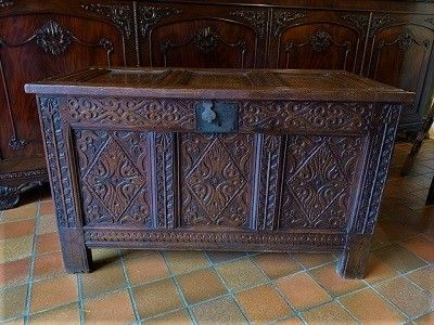 an early 18th century oak coffer with beautiful carved decoration and double panel ends