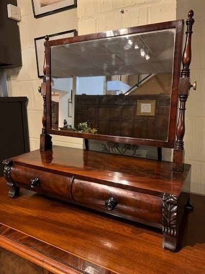 an early 19th century figured mahogany swing toilet mirror with 2 cushion drawers and carved acanthus decoration