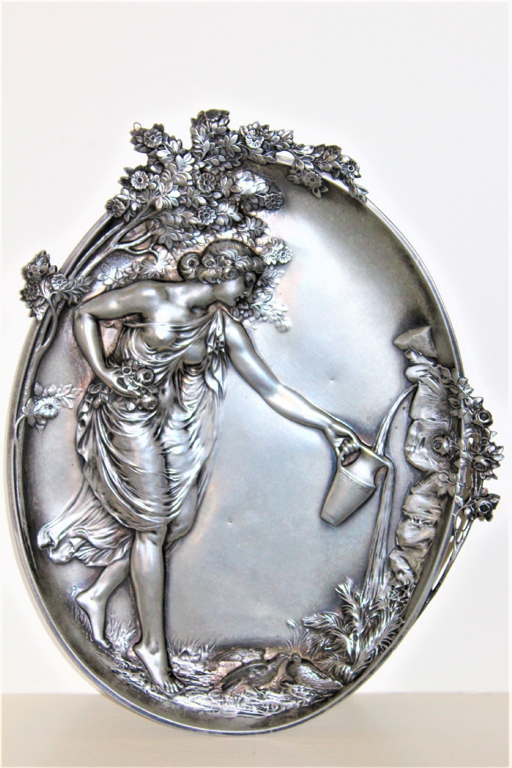 a fine large pewter art nouveau plaque depicting a beautiful maiden filling a ewer at a well continental circa 1890 to 1910 and small hall marks