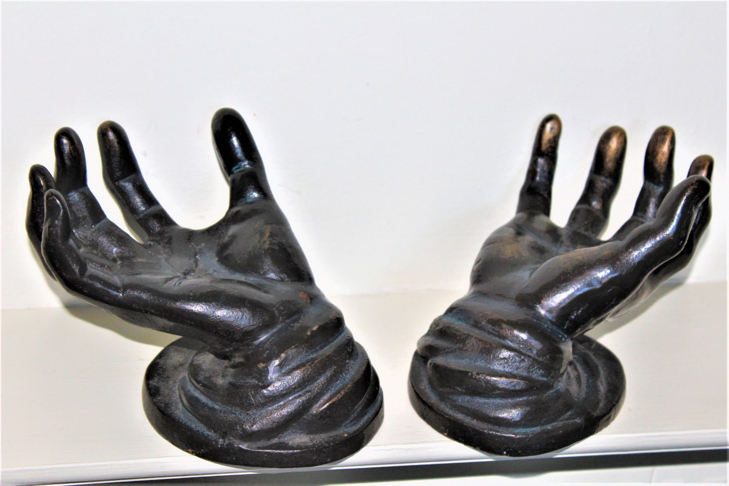 two cast solid bronze sculptures modelled as hands with palms turned up on a round base possibly english circa 1930 to 1960