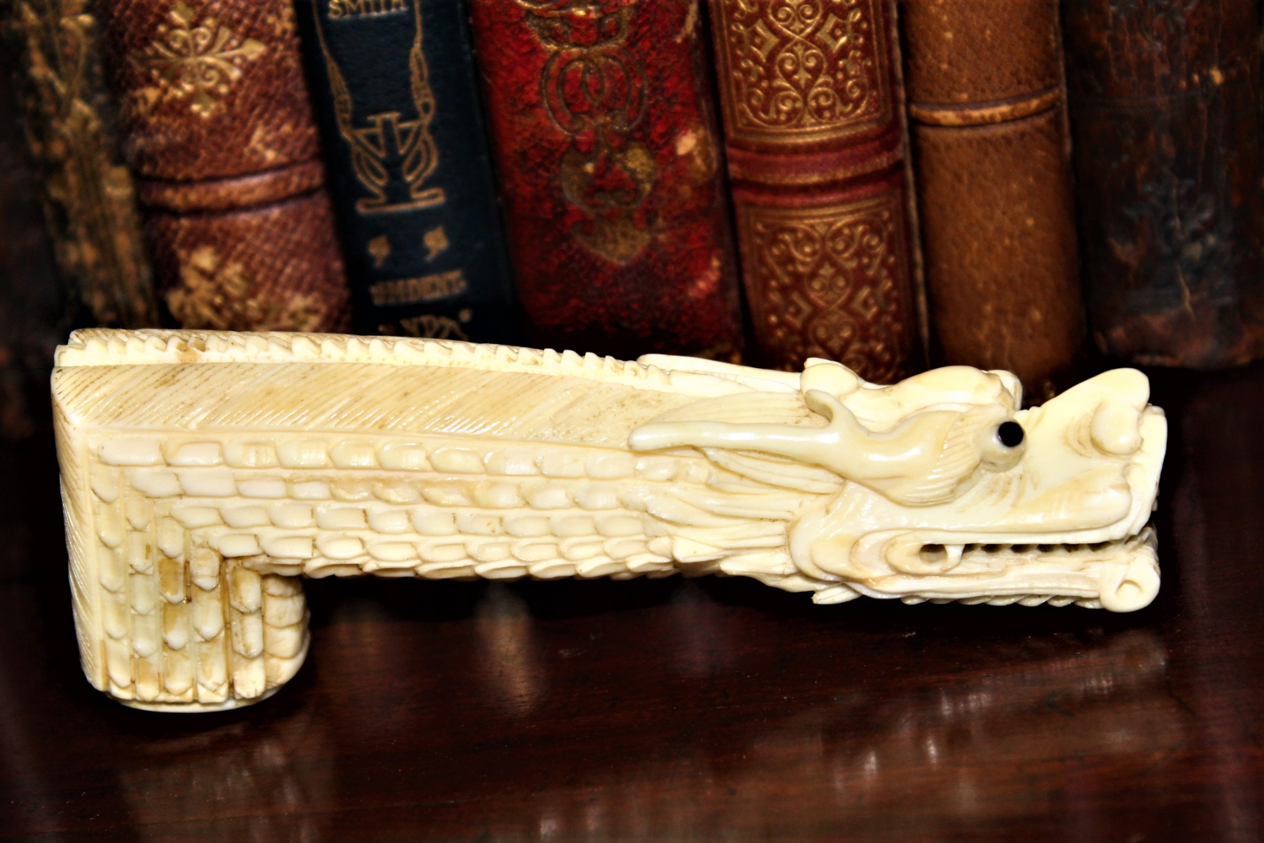 a chinese finely carved ivory walking stick handle depicting a dragon with a ball in its mouth
