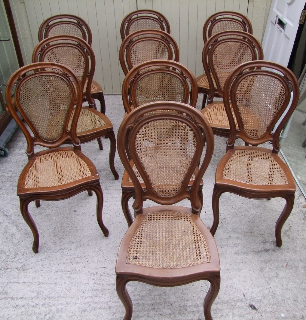 set of ten walnut dining chairs with cane backs and seats