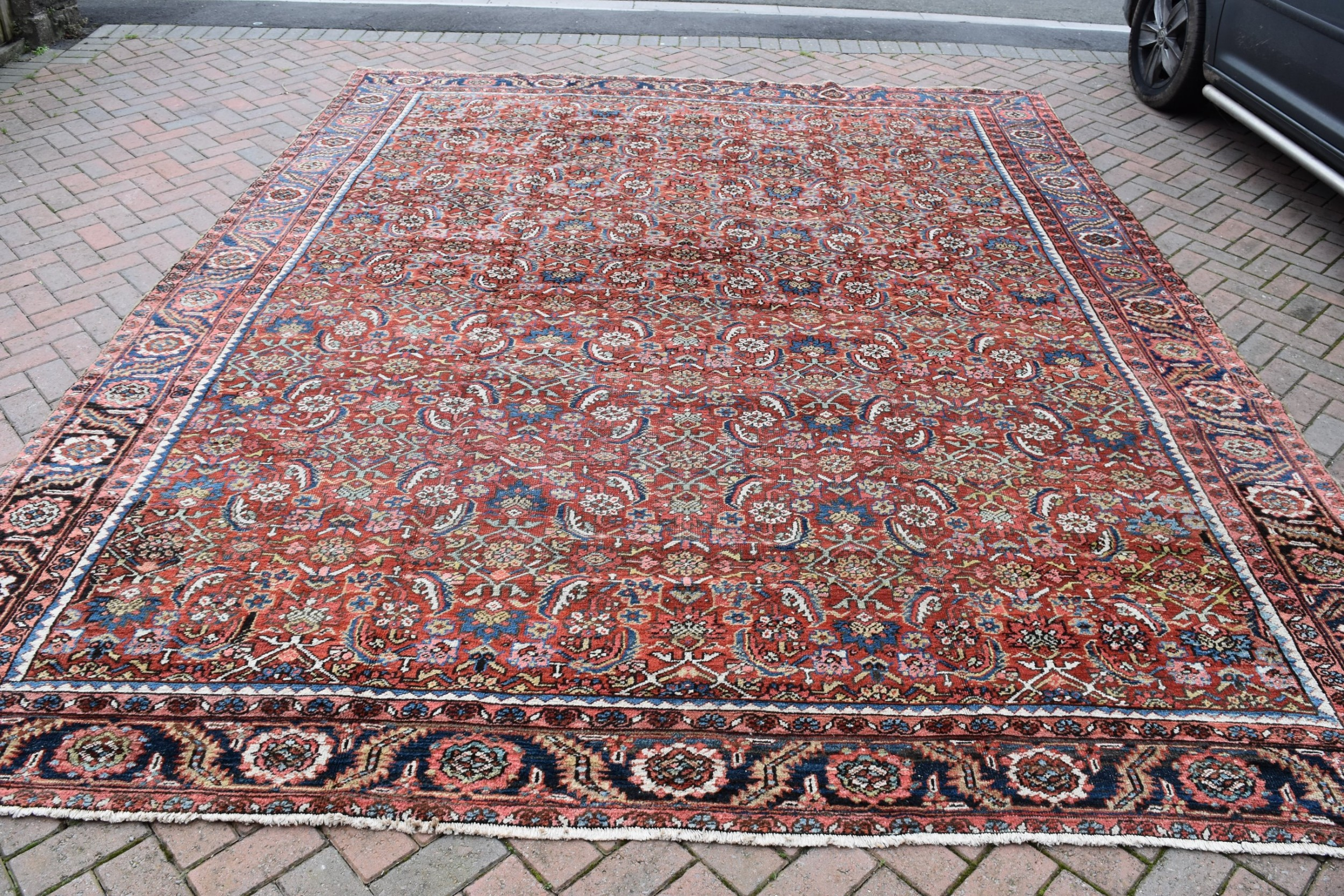 an antique persian heriz carpet 385x314cm