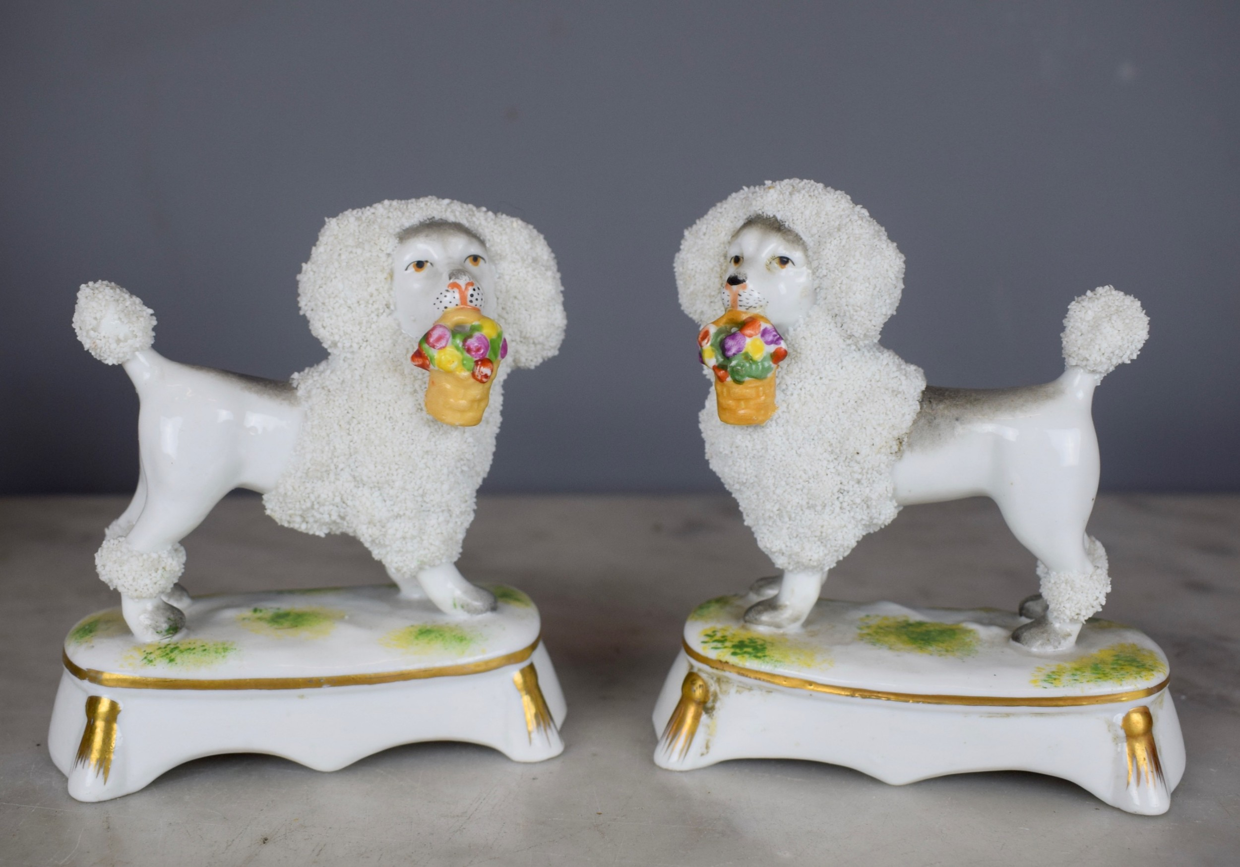 pair of french samson porcelain poodles carrying baskets in their mouths