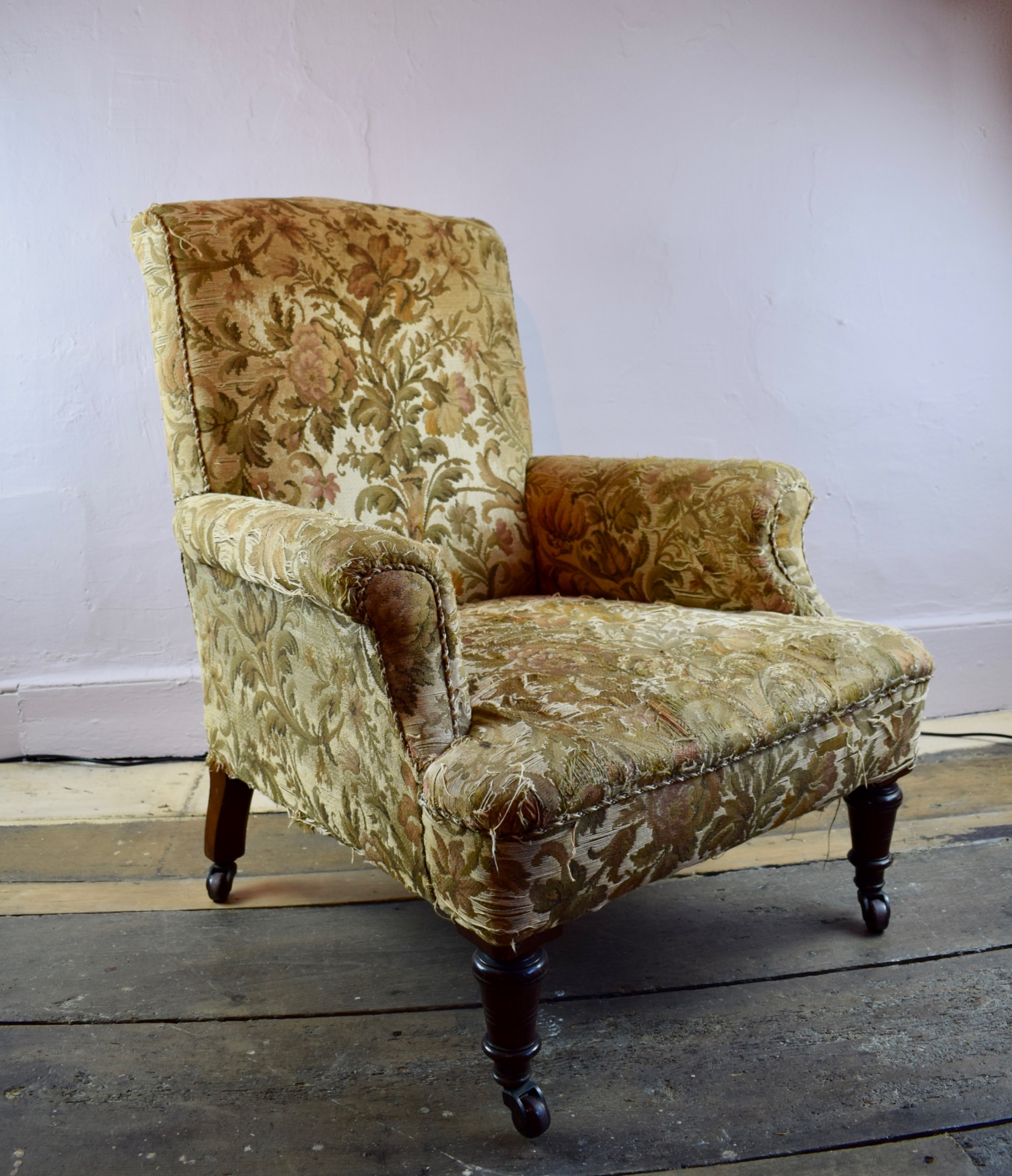 an antique library armchair with tapestry upholstery
