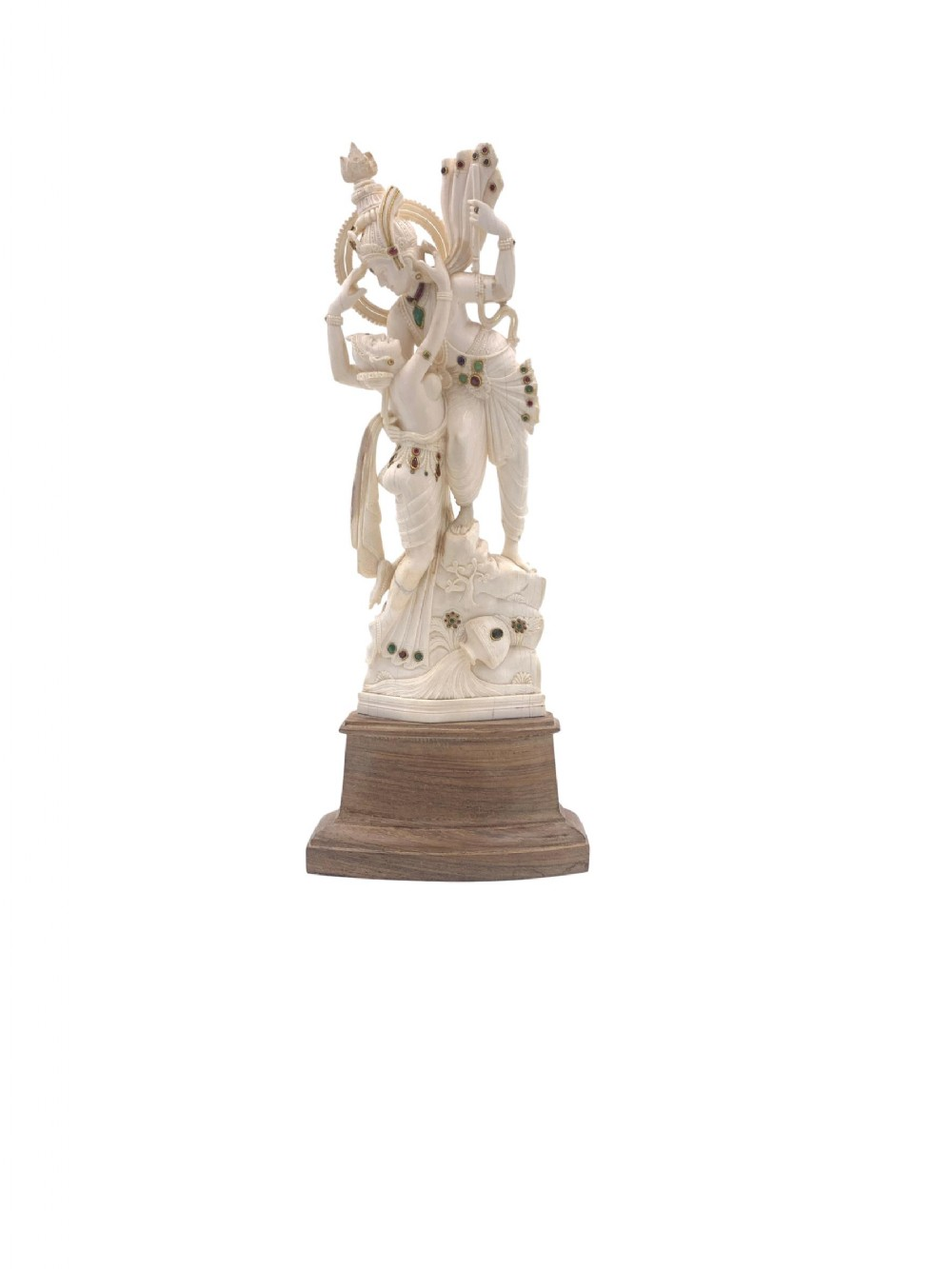 carved bejewelled indian ivory statue of embracing lovers radha and krishna raised on a wooden stand