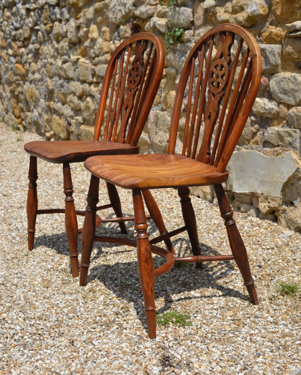 a pair of country yew and elm wheel back chairs with crinoline stretchers c 1800