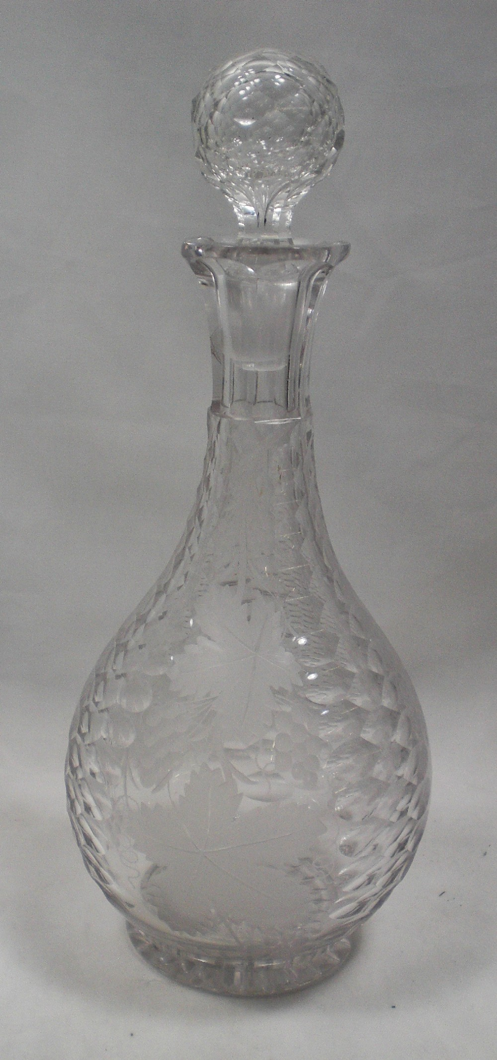 a crystal glass wine decanter engraved with panels of engraved vine leaves and scale cutting english c1860