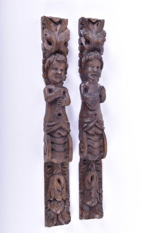 pair of carved oak wall hangings showing musicians
