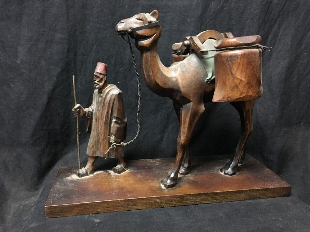 carved wooden man leading a camel