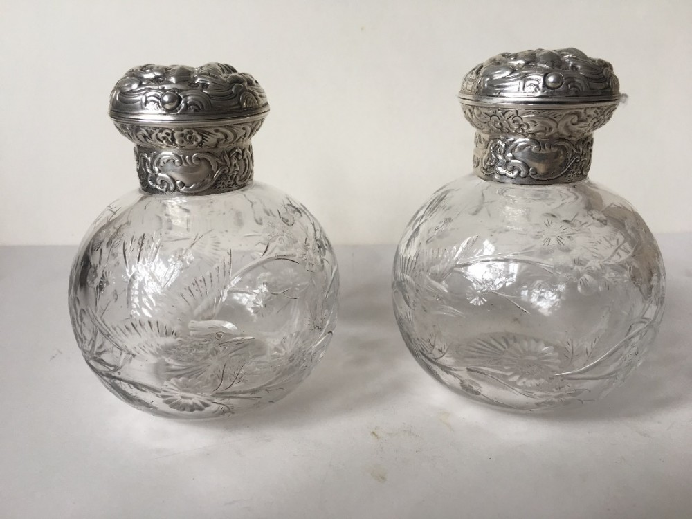 a pair of silver topped hm perfume bottles