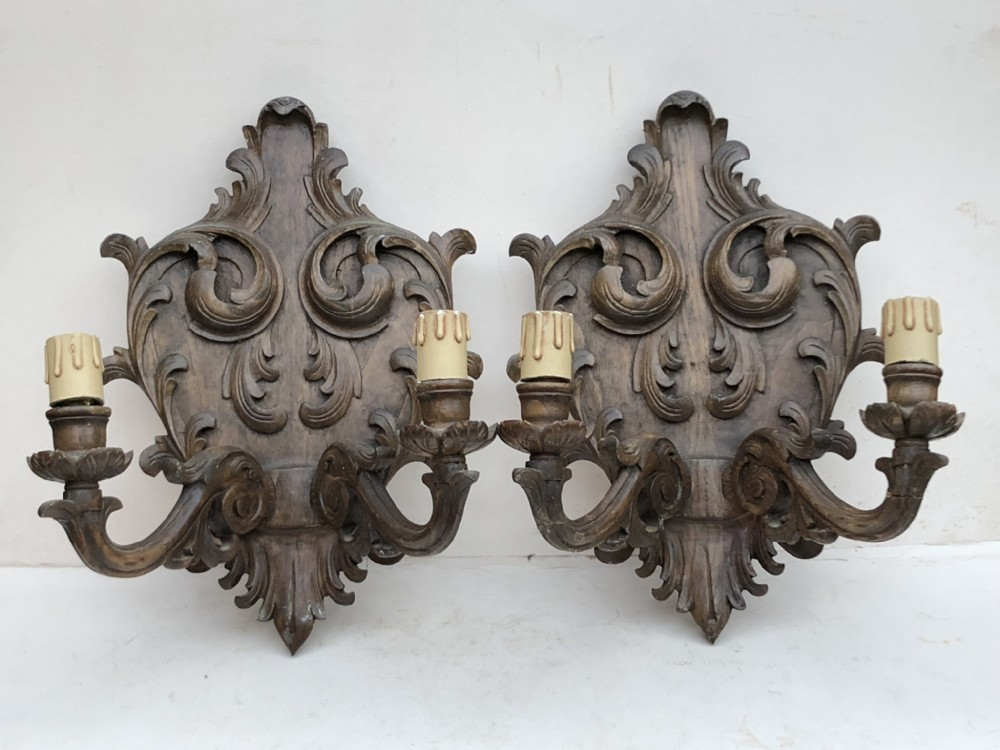 a pair of carved walnut wall lights