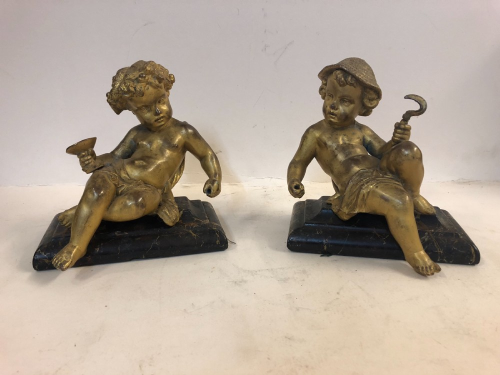 pair of gilt metal cherub ornaments on marble bases
