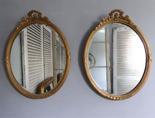 pair of gilt oval antique mirrors