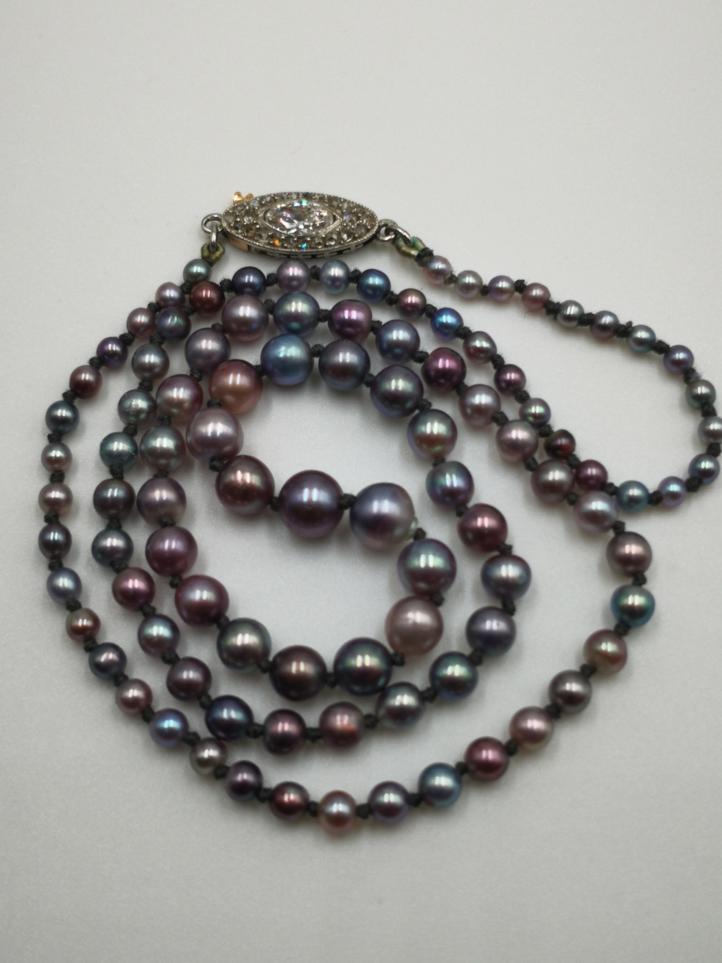 a multicolor natural pearl necklace with diamond and gold clasp circa 1900 with cert