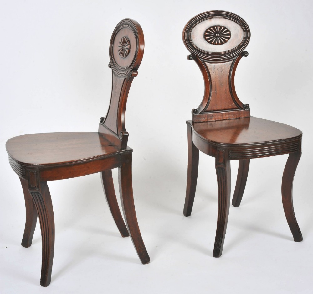 pair of regency carved mahogany hall chairs