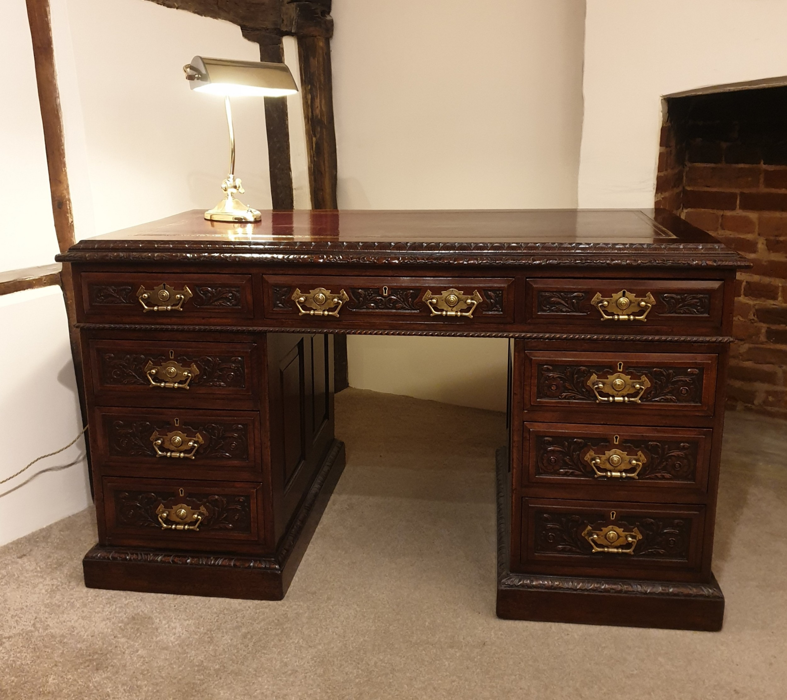a finely carved panelled mahogany pedestal desk