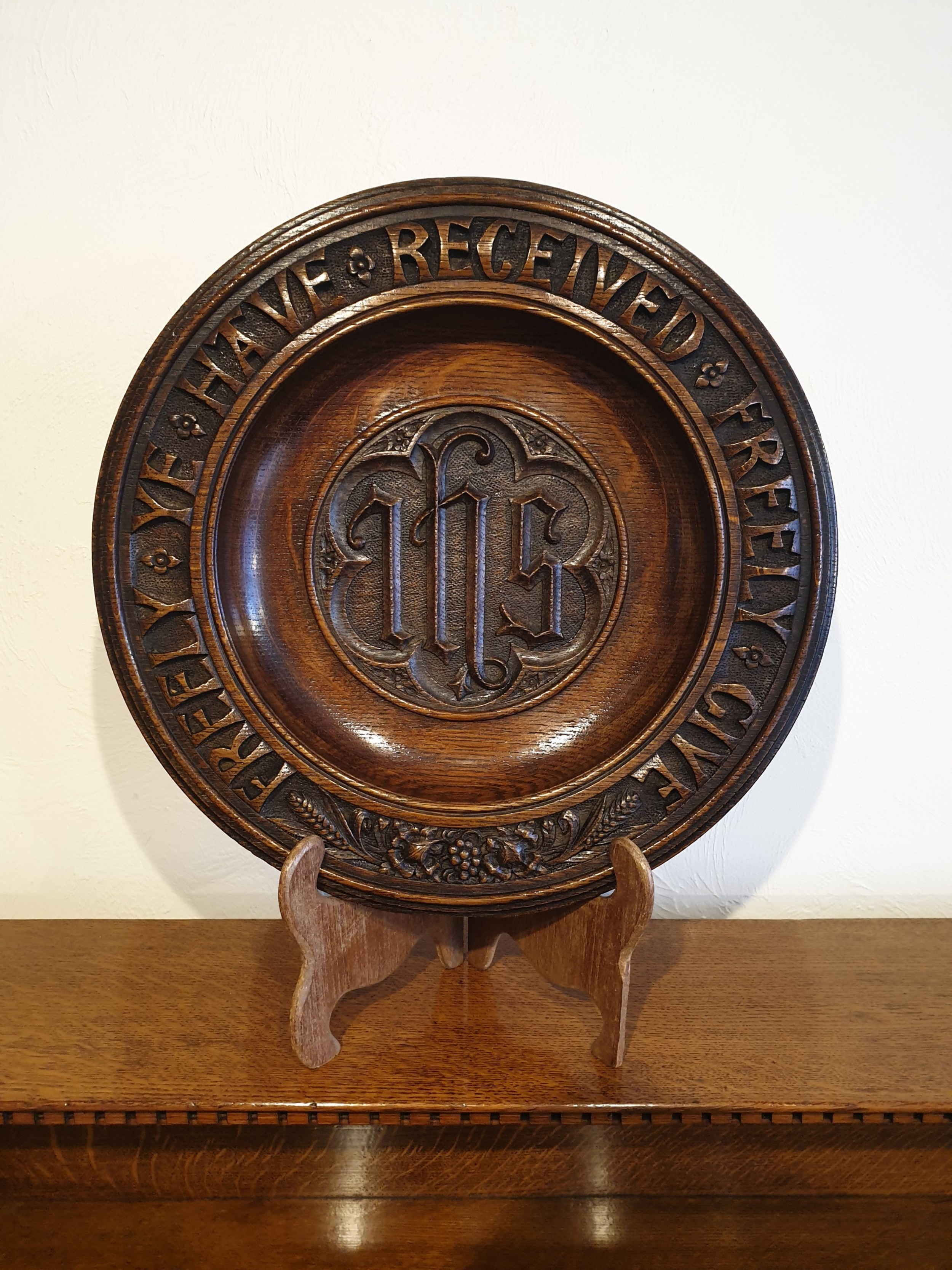 an finely carved and decorated oak alms dish