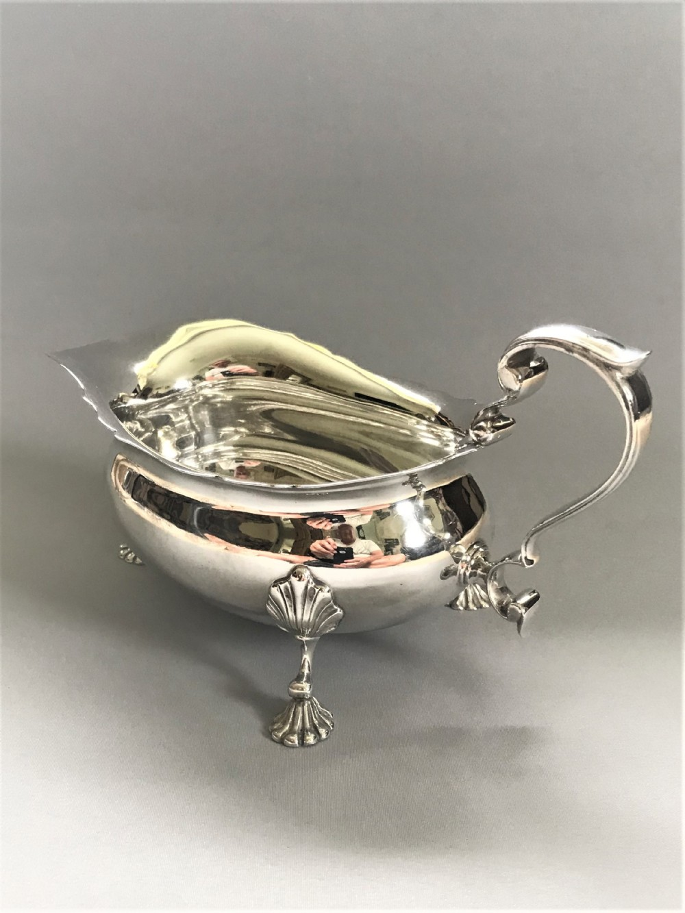 an imposing large silver gravy boat