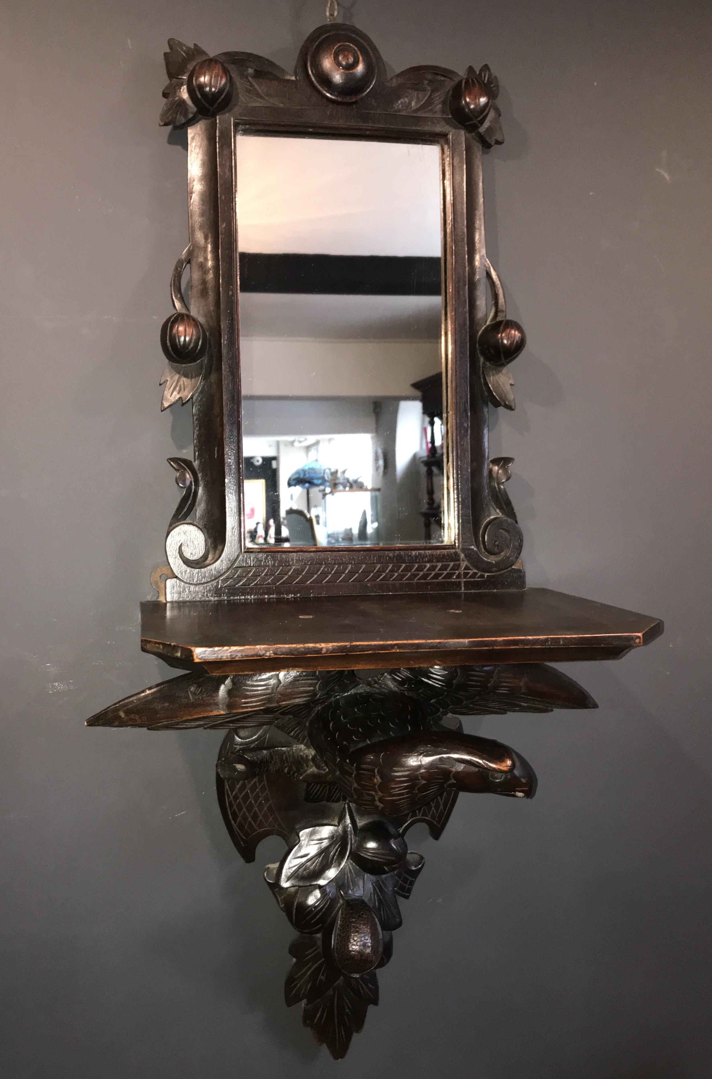 a walnut mirrored backed bracket shelf supported by a spread eagle