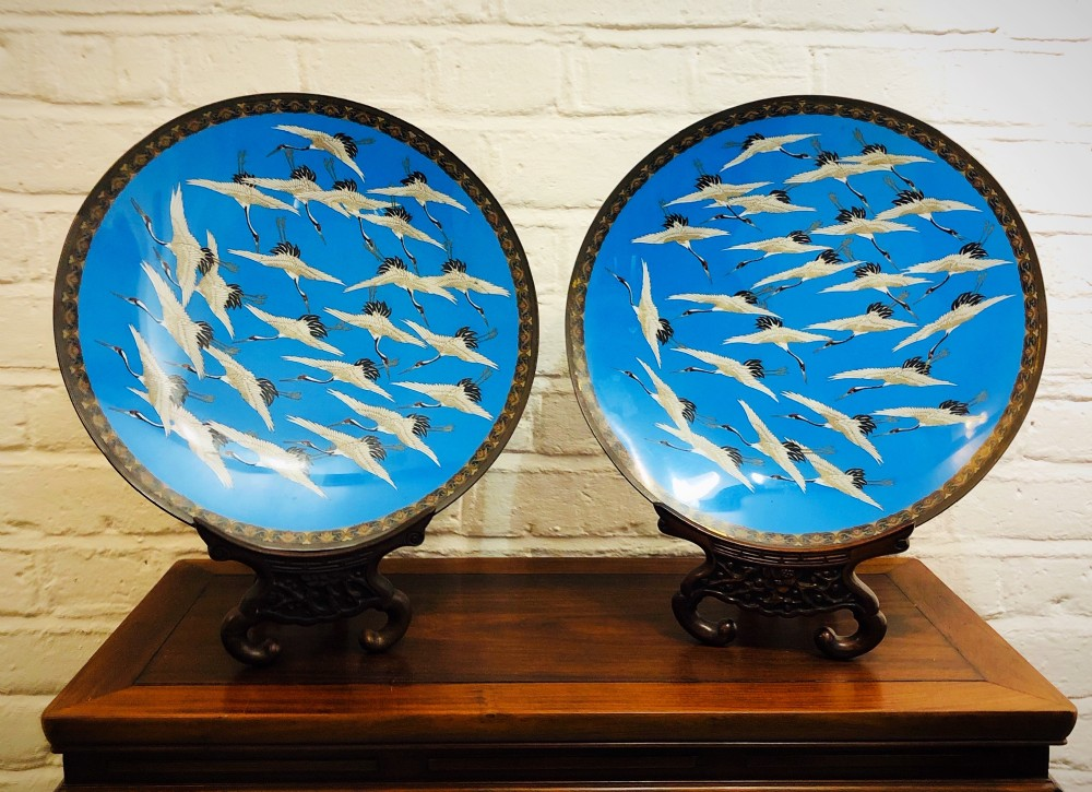 a pair of japanese cloisonne dishes showing a flock of redcapped cranes in flight