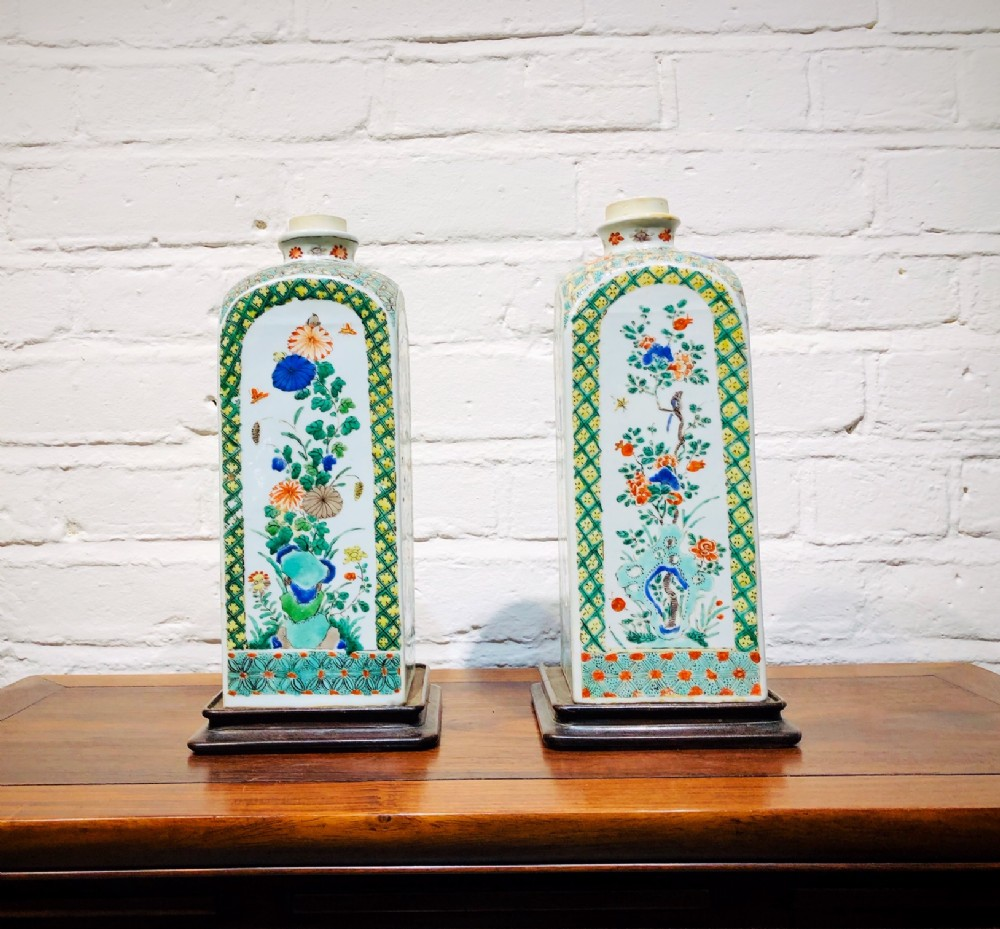a pretty pair of antique chinese famille verte canisters with wooden stands circa 1700