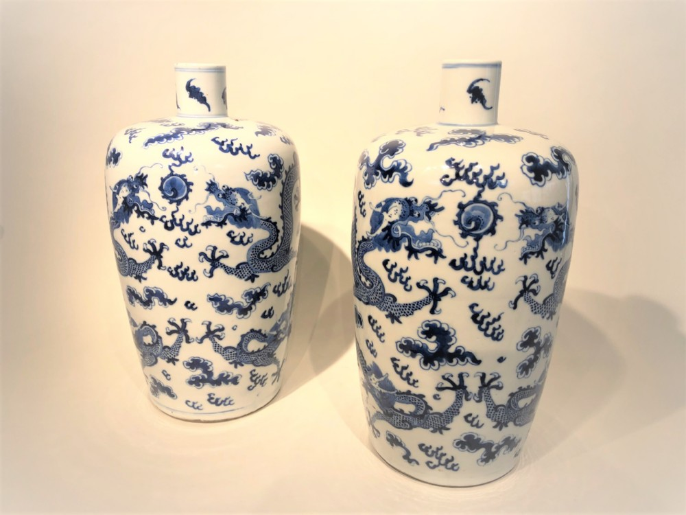a highly decorative pair of antique blue and white chinese bottle vases