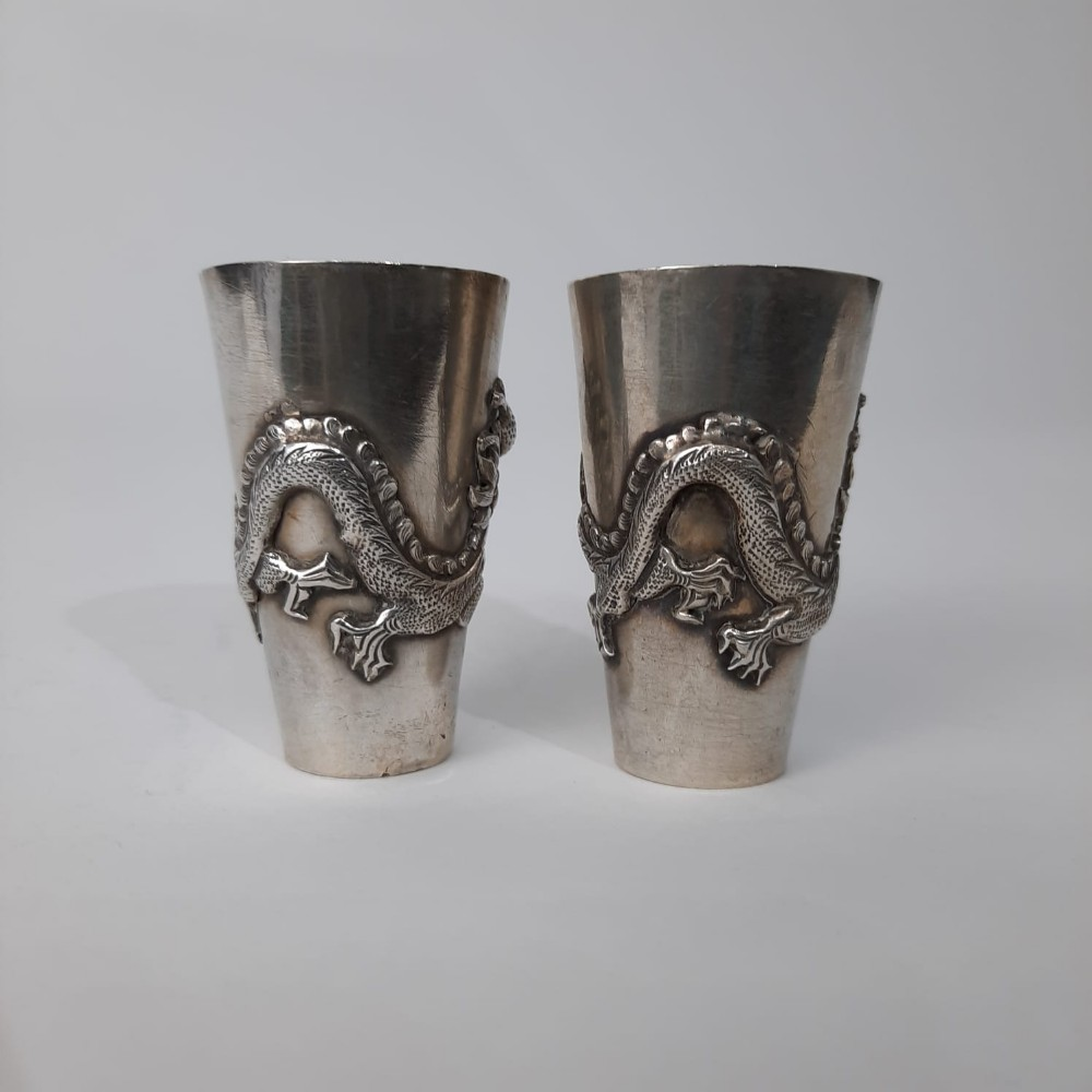 a pair of chinese silver shot glasses