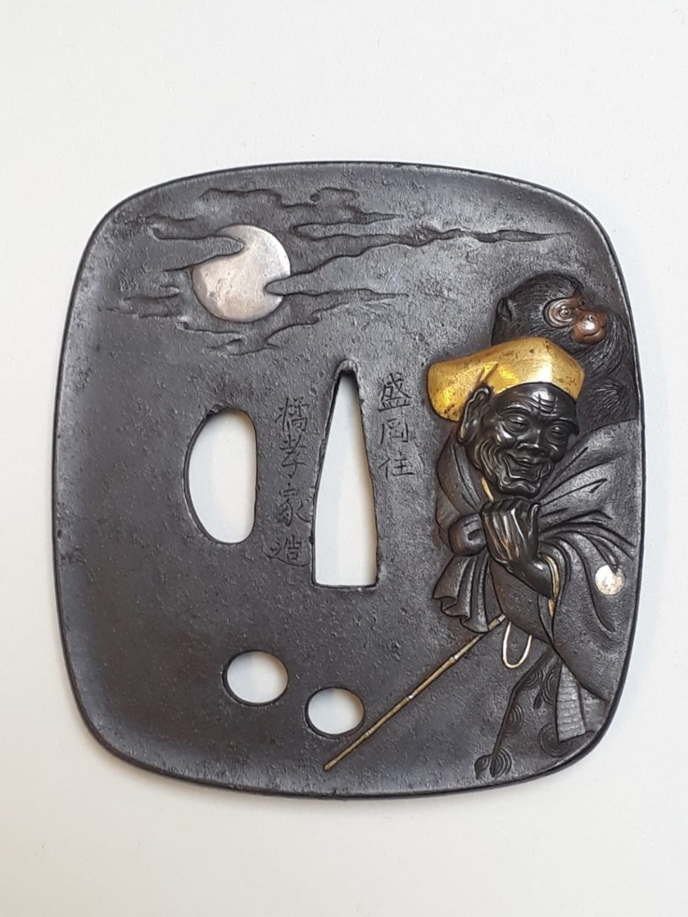 a japanese meiji period iron tsuba decorated with a monkey trainer