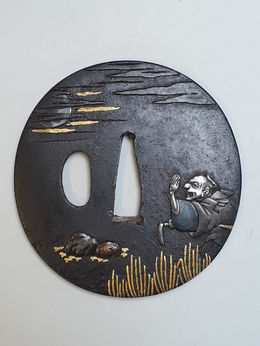a japanese meiji period iron tsuba with multimetal decoration of a reed cutter
