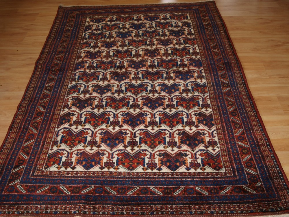 old persian afshar rug with repeat shield design on an ivory ground circa 1920