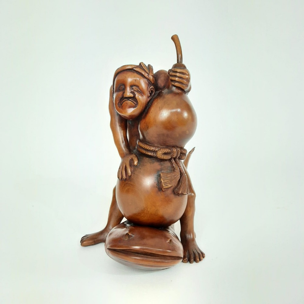 japanese wood carving of a fisherman with a huge fish