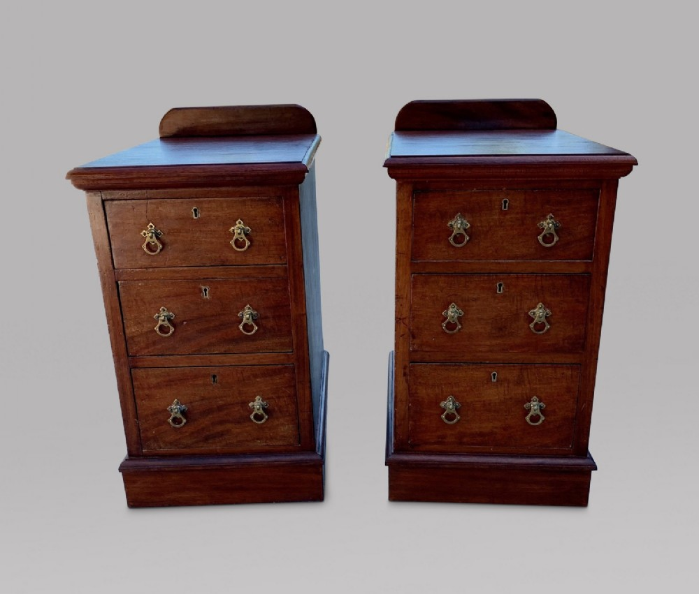 a pair of three drawer mahogany bedside tables