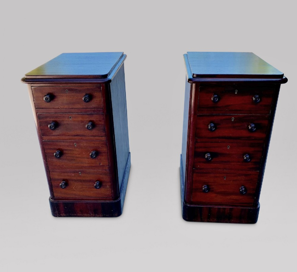 a pair of four drawer mahogany bedside tables