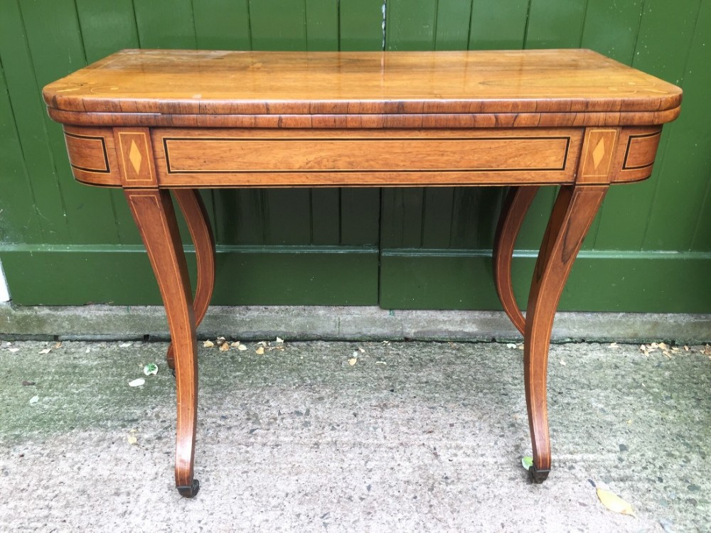 early c19th regency period inlaid rosewood foldover cardgames table raised on sabre legs