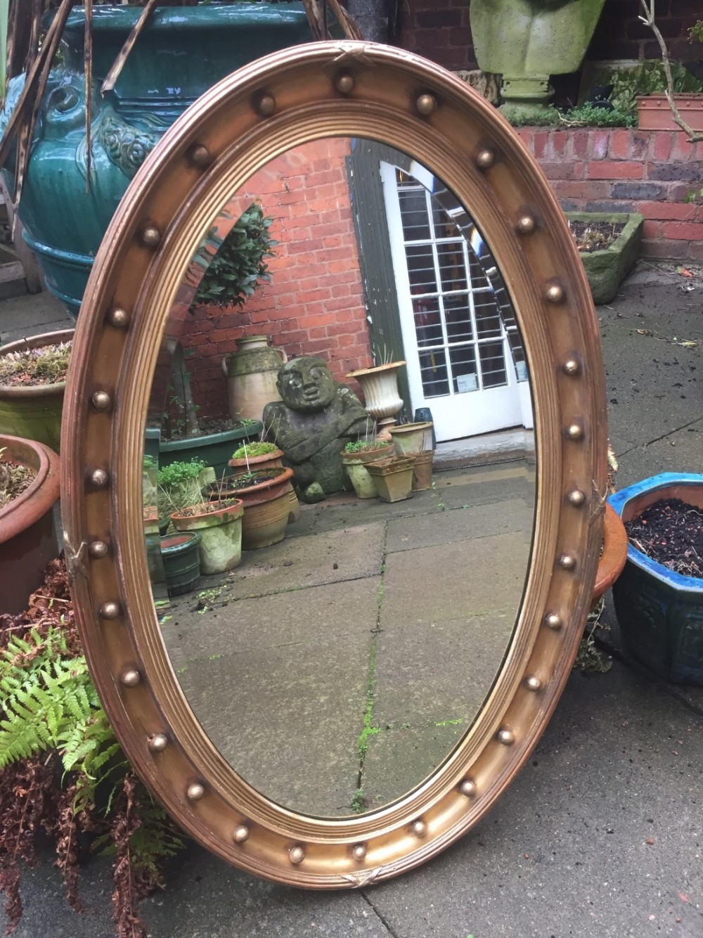 late c19th oval giltwoodframed mirror in the regency style