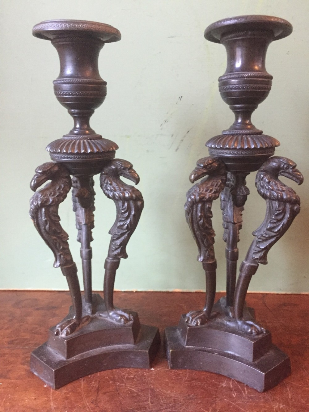 pair of early c19th george iv period bronze candlesticks on triform stylised eagle or griffin supports