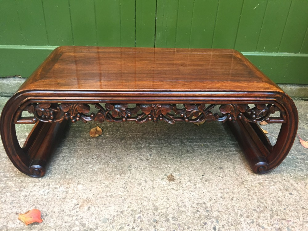 late c19thearly c20th chinese qing dynasty carved hardwood low 'kang' or opium table of scrollend form