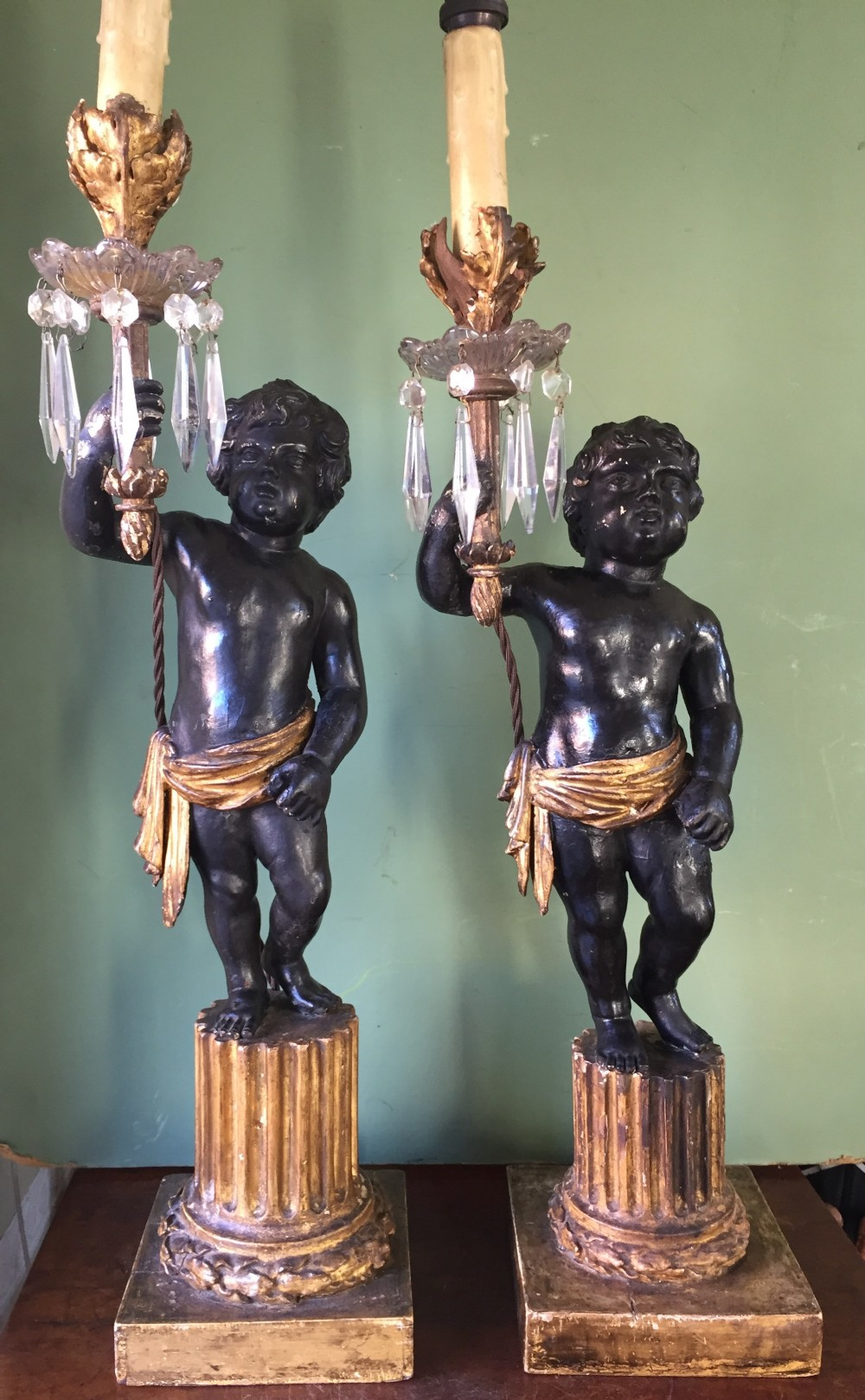 pair of early c19th italian carved wood amorini or cherubs modelled as lamps raised on truncated fluted column bases
