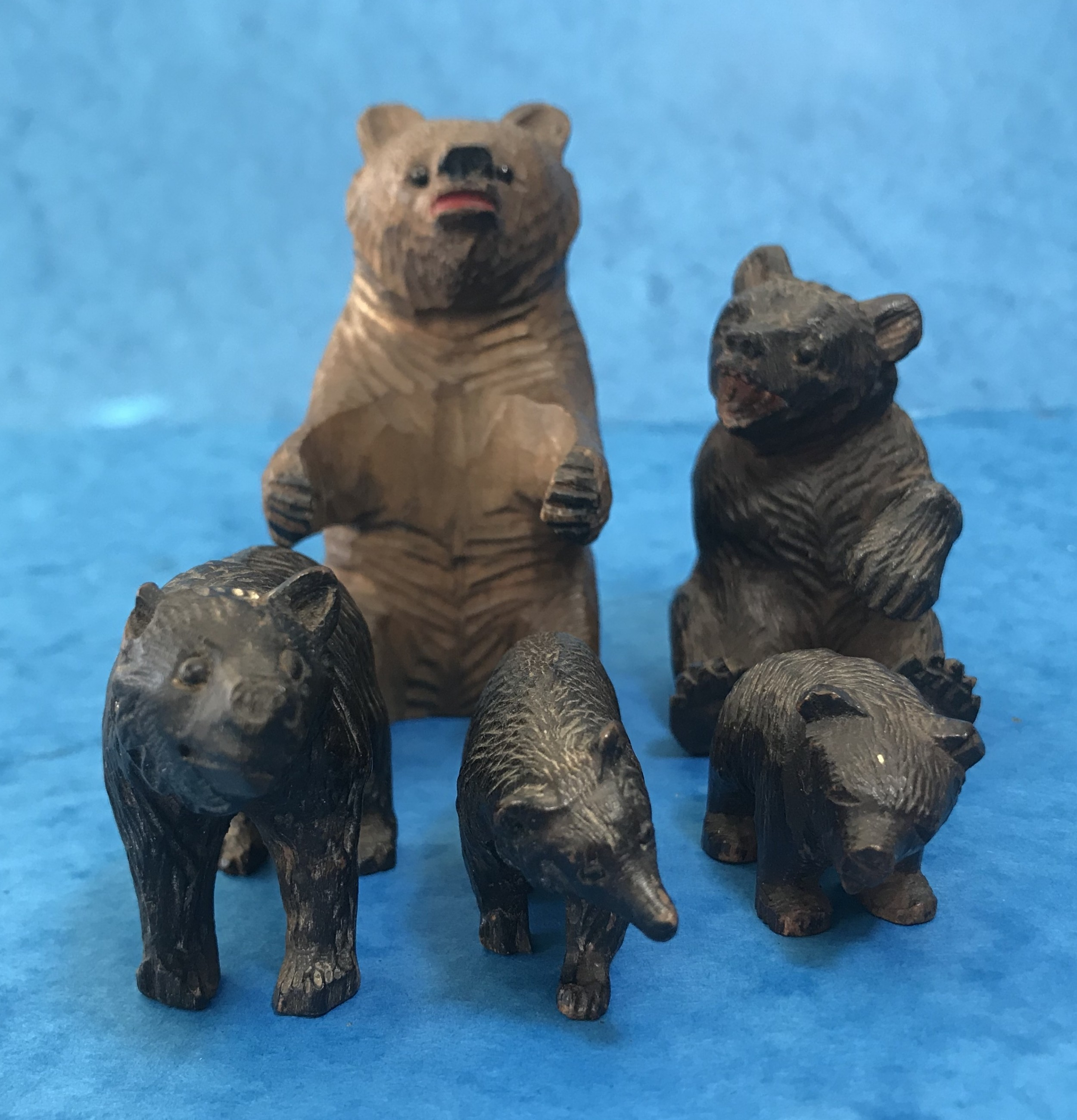 a small collection of carved black forrest bears
