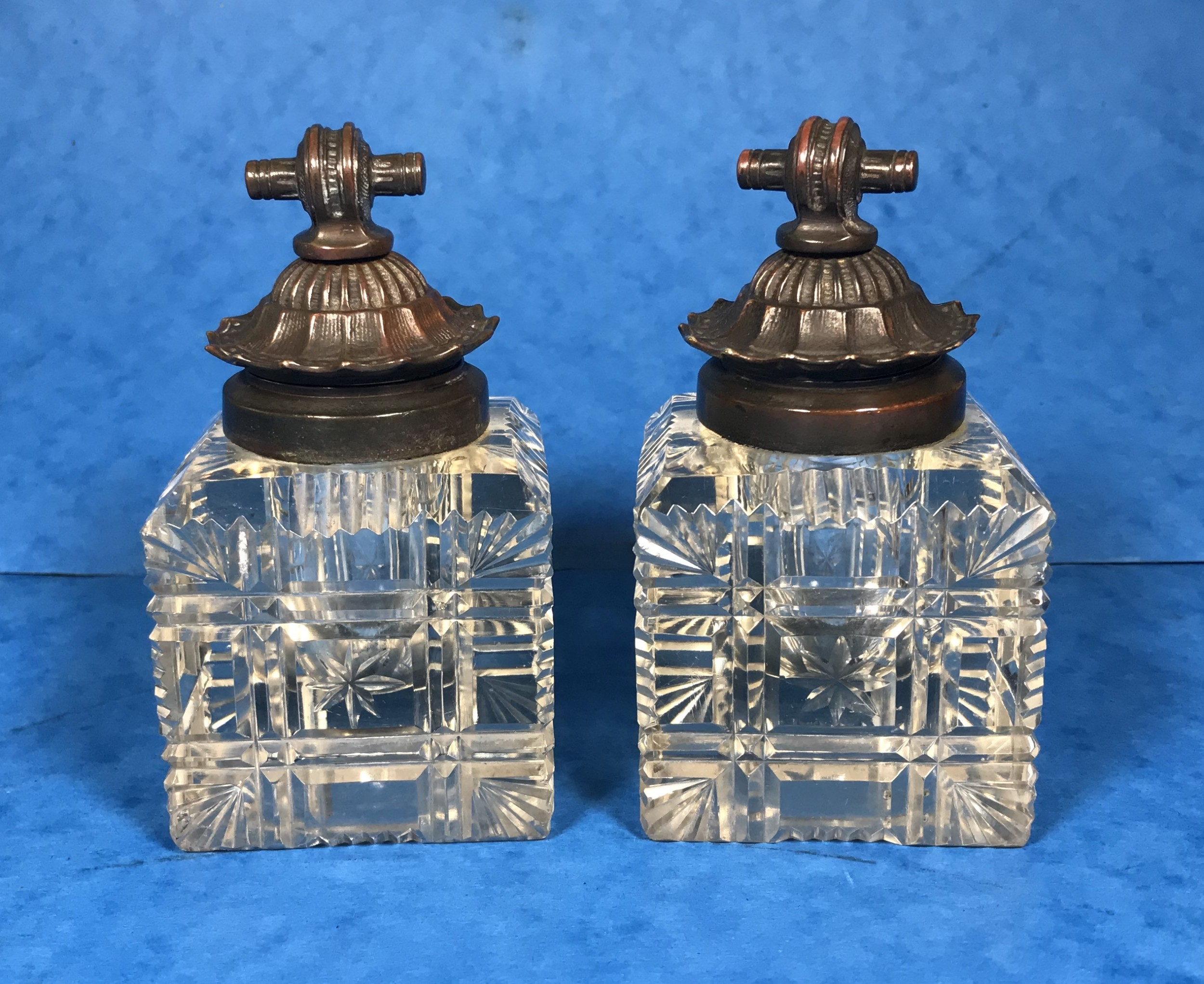 a pair of cut glass inkwells with bronze lids