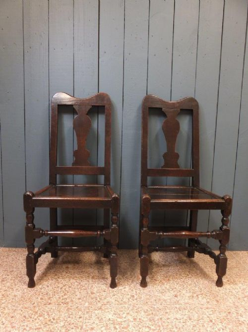 a pair of country oak chairs