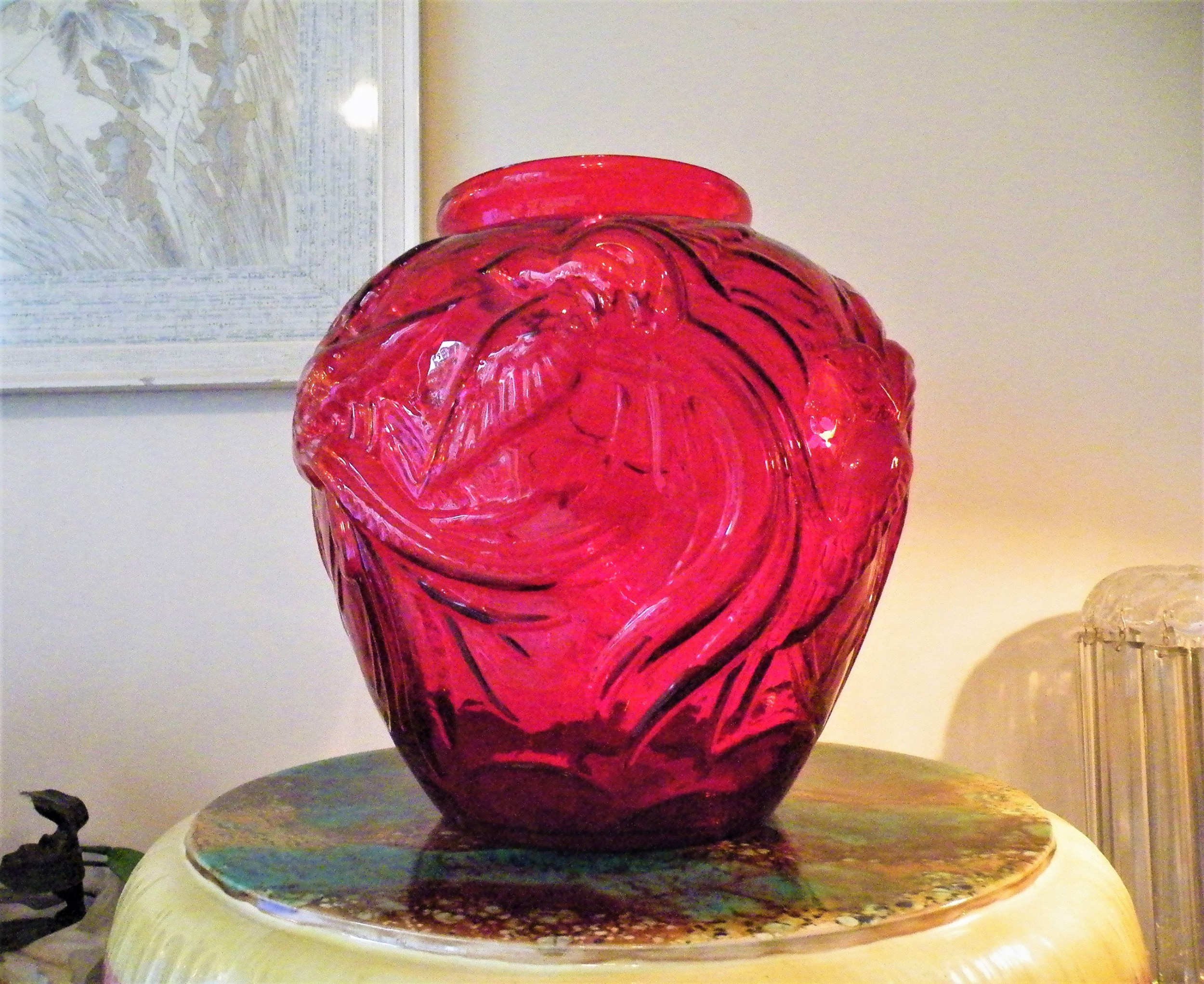 a large art deco red glass vase embossed with flying birds