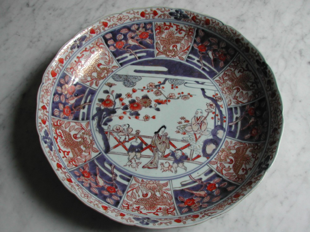 japanese large imari dish decorated with figures and dogs in a landscape 18th century