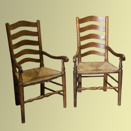 A Pair Of Arts And Crafts Rushseated Oak Ladderback Carver Chairs