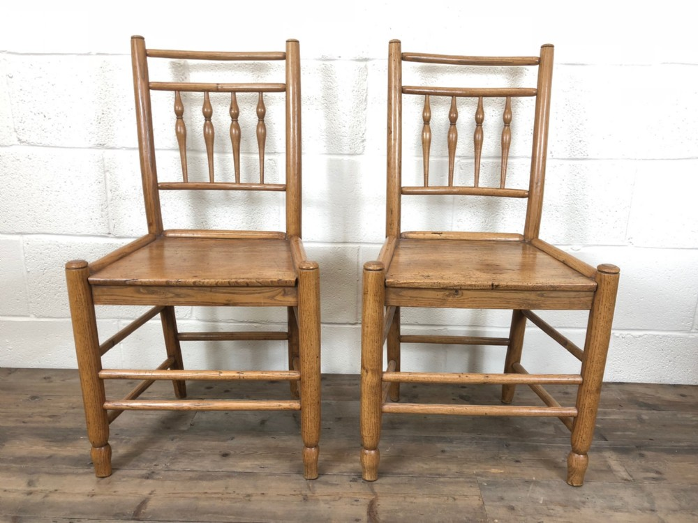 pair of light coloured comb back chairs