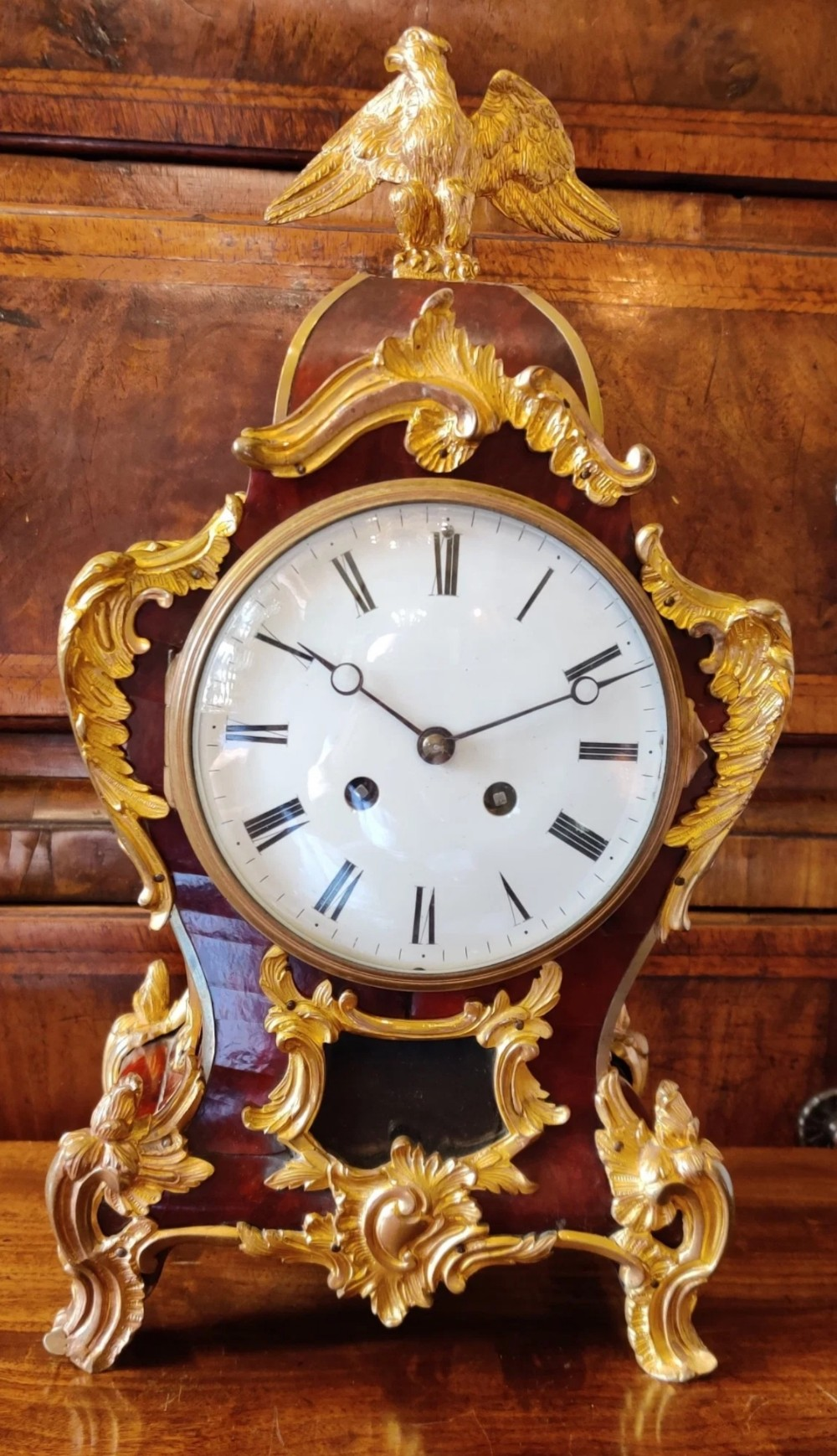 a red tortoiseshell and waisted mantel clock