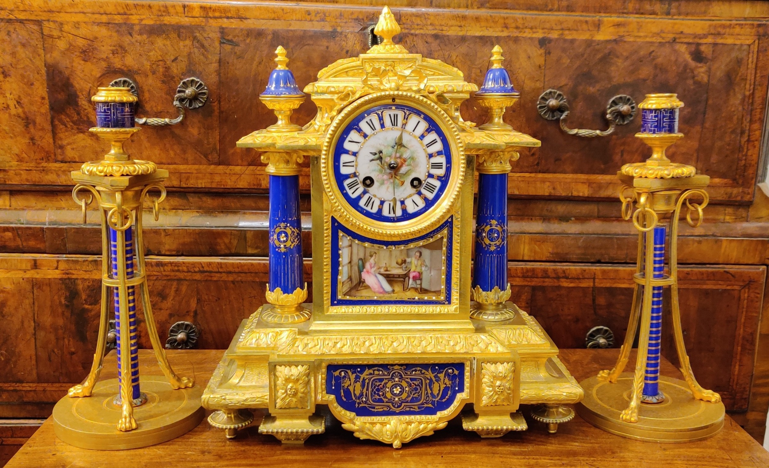french gilt bronze porcelain and ormolu mantel clock garniture with medium blue sevres style porcelain decoration and plaques