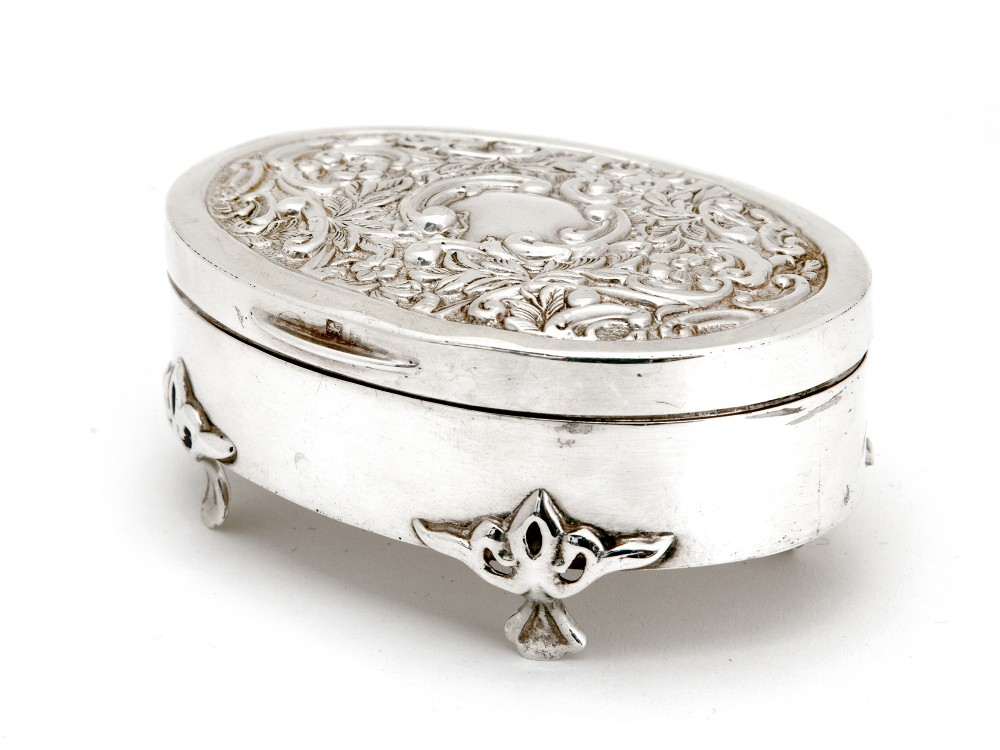 oval edwardian silver jewellery box with a hinged lid decorated with scrolls and flowers